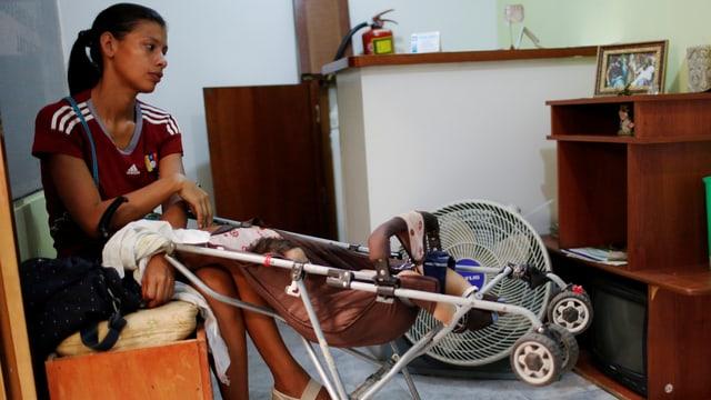 Venezolanerin sitzt mit ihrem Kind in Wartesaal