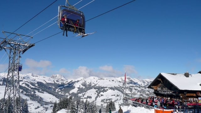 Eine Sesselbahn in der verschneiten Landschaft von Gstaad.