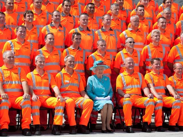 Inmitten von sitzenden Arbeitern mit orangen Kleidern, sitzt die Queen mit einem hellblauen Mantel.
