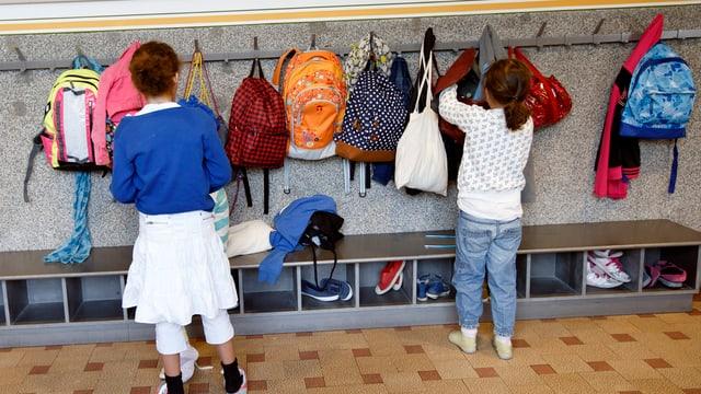 Zwei Mädchen von hinten in einer Schulgarderobe