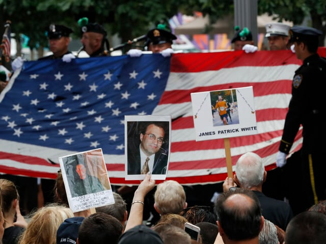 Polizisten tragen eine grosse USA-Flagge. Angehörige der 09/11-Opfer halten Fotos ihrer Liebsten hoch.