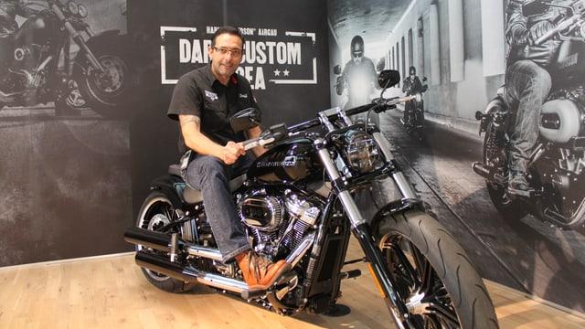 Der Chef der des Harley-Shops posiert auf einer Harley