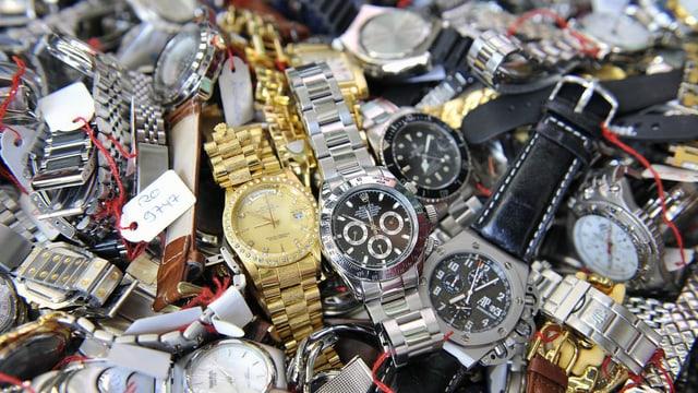 Viele sichergestellte, gefäschte Uhren auf einem Haufen.