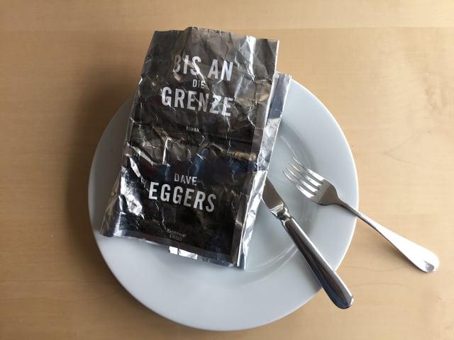 Das zerknüllte Cover von Dave Eggers neuem Roman «Bis an die Grenze» auf weissem Teller