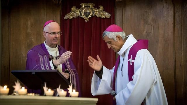 Zwei Kirchenmänner am Altar.