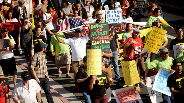 Demonstrants cun placats e bandiera americana