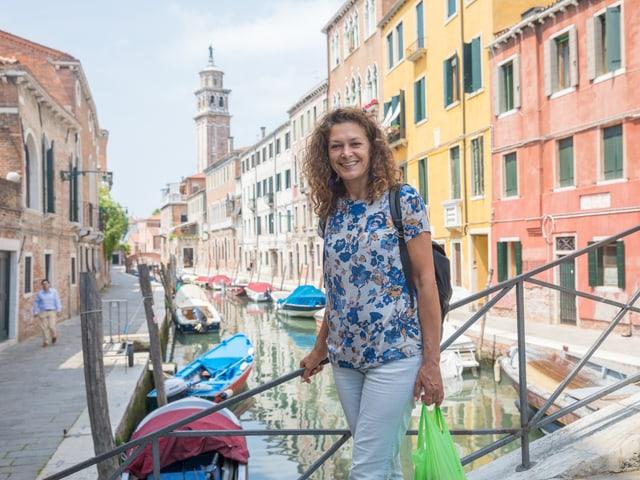 Eine Frau mit Einkaufstüte steht auf einer Brücke