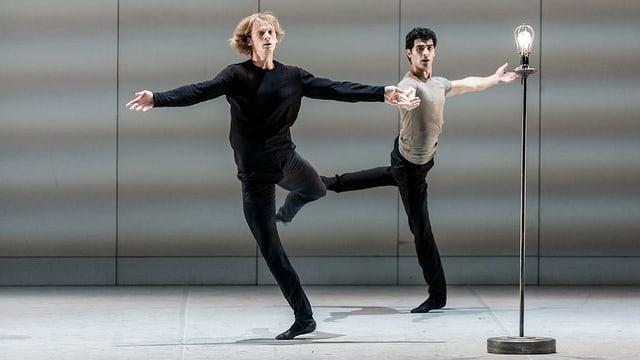 Zwei Künstler tanzen um eine Stehlampe.