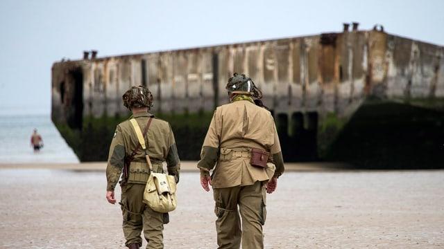 Zwei Männer in US-amerikanischen Uniformen gehen am Strand entlang in Richtung eines Landesteges aus dem zweiten Weltkrieg.