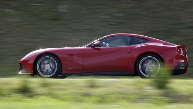 Ein Ferrari fährt auf einer Strasse.