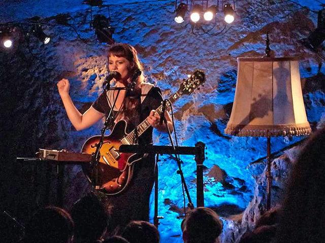 Frau mit Gitarre auf der Bühne