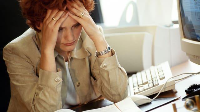 Eine Frau sitzt an ihrem Computer, den Kopf in die Hände gestützt.