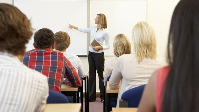 Eine Lehrerin doziert vor Erwachsenen.