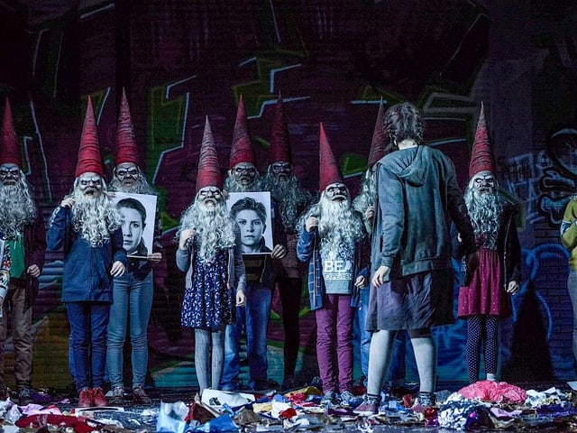 Zwerge in blauen Kleidern und mit lila, spitzigen Hüten. Davor steht Gretel.