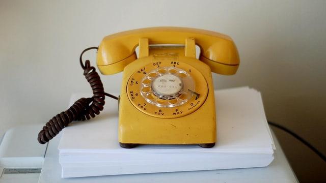 Gelbes Telefon mit Wählscheibe auf einem Stapel Papier.