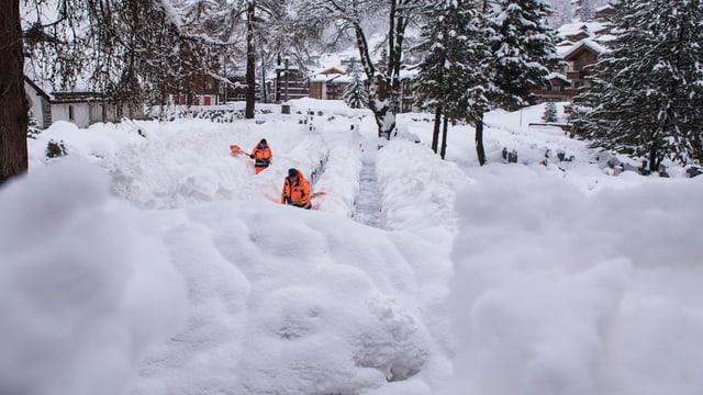 Männer schaufeln im Schnee.