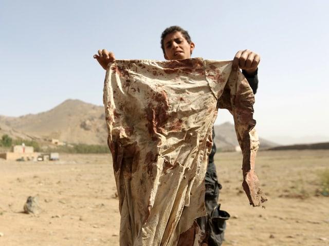 Junge hat blutbeflecktes Kleidungsstück in die Kamer.