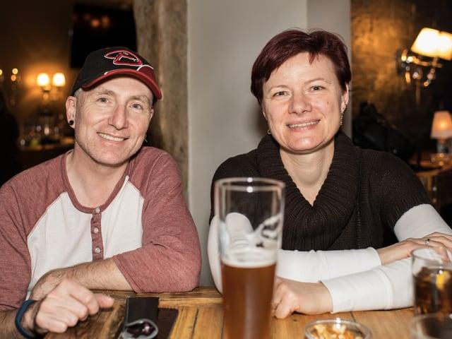 Ein Mann und eine Frau im mittleren Alter sitzen an einer Bar und schauen lächelnd in die Kamera. vor ihnen steht ein grosses Glas Bier. Er trägt eine Baseballmütze, sie einen Kurzhaarschnitt.