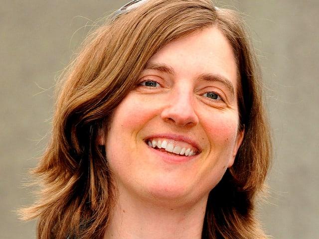 Porträt einer jungen Frau mit braunen Haaren und einer Sonnenbrille auf dem Scheitel.