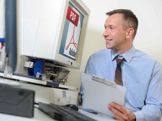 Ein Mann schaut lachend auf einen Computerbildschirm, auf dem das PDF-Logo zu sehen ist.