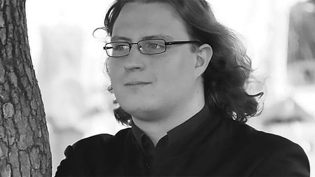 Schwarz-Weiss-Fotografie von einem Mann mit schulterlangen Haaren und Brille.