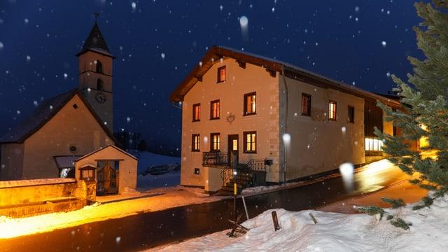 Haus und Kirche in der Nacht, es schneit etwas.