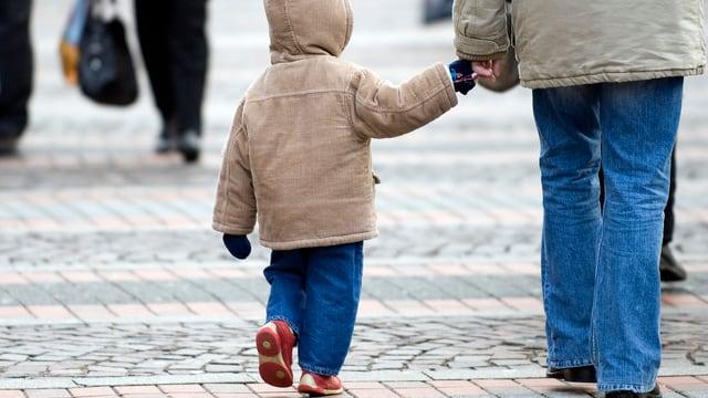 Eine Person hält ein Kind an der Hand.