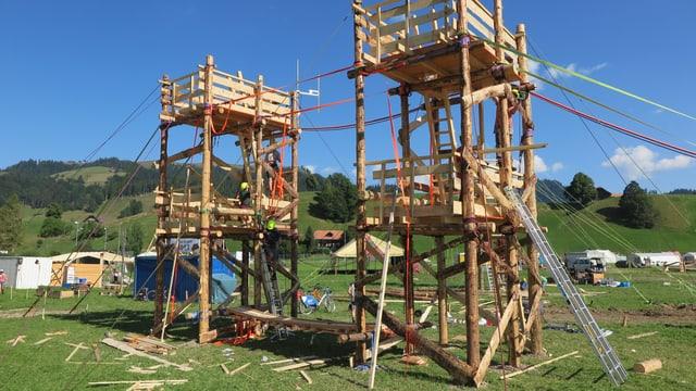 Zwei hohe Holztürme auf einer Wiese markieren den Eingang zum Pfadilager «LUpiter18» in Escholzmatt