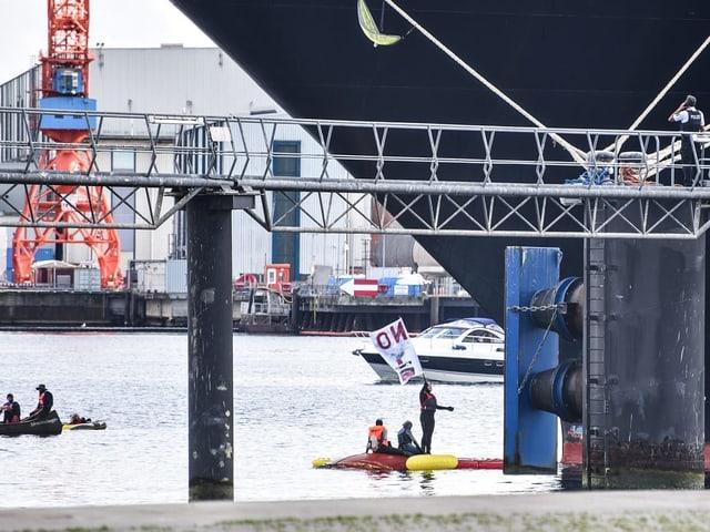 Blick auf den Kieler Hafen und Aktivisten in einem Schlauchboot vor dem Kreuzfahrtschiff