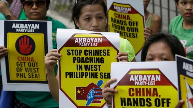 Philippinische Demonstrantinnen halten Protestschilder in der Hand