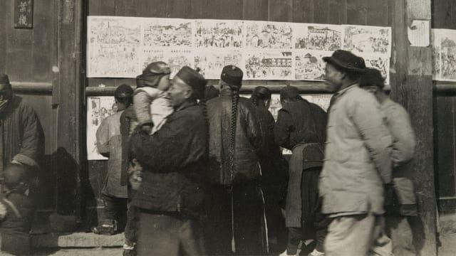 Menschen stehen vor chinesischen Drucken