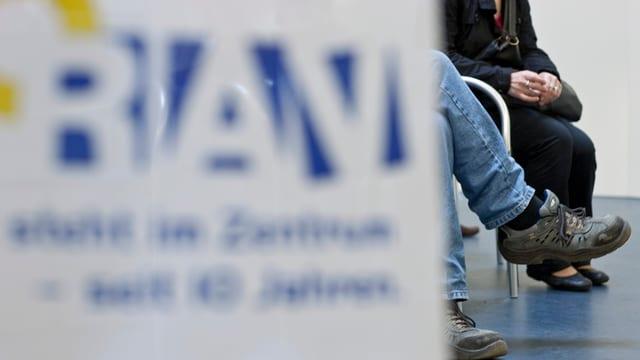 Menschen sitzen in einem Wartsaal, im Vordergrund das «RAV»-Logo.