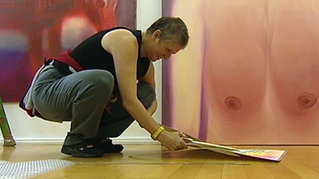 Eine Frau schenidet gebückt ein grosses Stück Papier. Im Hintergrund ist ein Gemälde mit Brüsten zu sehen.