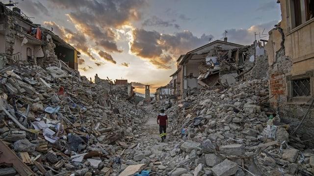 Eine Rettungskraft läuft durch das zerstörte Amatrice.