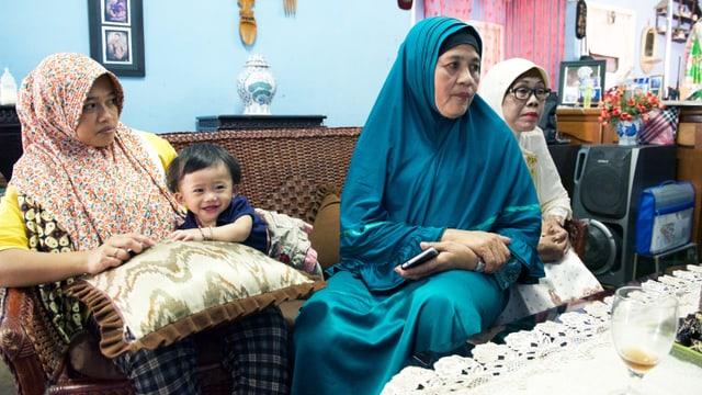 Zulbaidah sitzt mit zwei Frauen auf dem Sofa.