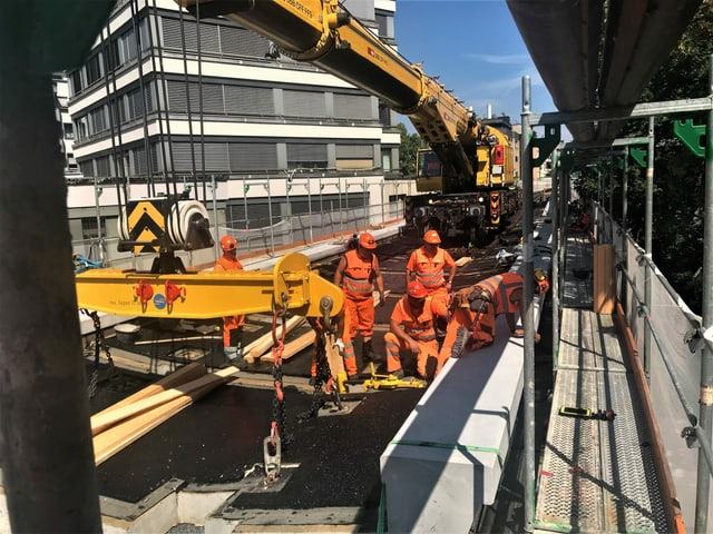 Ein Brückenbaukran der SBB liefert die Betonelemente per Schiene an.