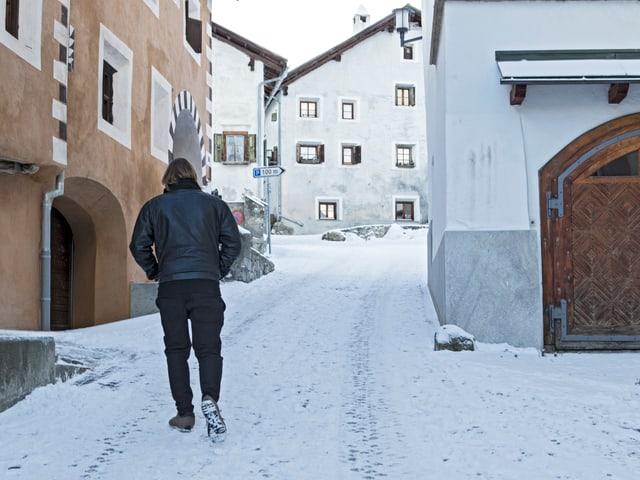 Ein Mann geht in einem Dorf auf einer schneebedeckten Strasse