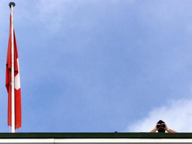 Ein Mann schaut von einem Hausdach mit durch ein Fernrohr in die Kamera. Links eine Schweizer Fahne.