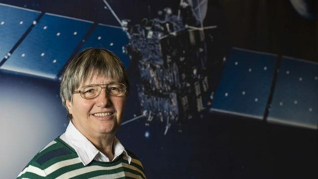 Frau mit Brille und kurzen grauen Haaren vor einem Satellit.
