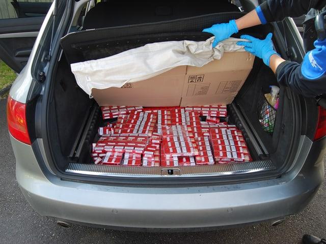 Im Reserverad-Kasten eines Autos versteckte Zigaretten.