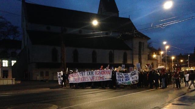 Demonstrationszug mit farbigen Bannern und Schriftzügen vor der Matthäuskirche in Kleinbasel.