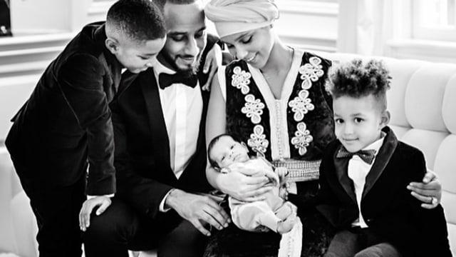 Alicia Keys mit Baby auf dem Schoss, zwei Buben, und ihrem Mann, der neben ihr sitzt.
