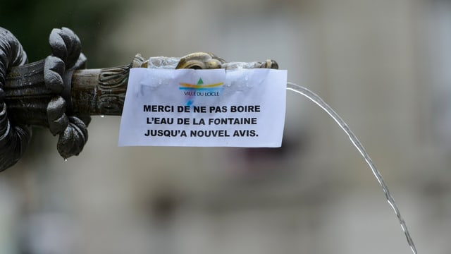 Ein Brunnen in Le Locle, mit einem Aufkleber wird vor dem verunreinigten Wasser gewarnt.