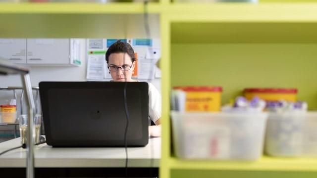Pflegerin an einem Laptop