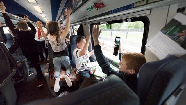 Kinder in einem Zug springen auf.