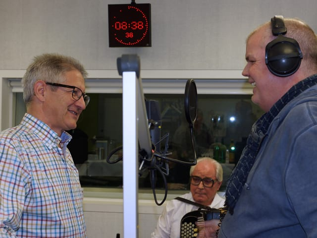Zwei Männer an Mikrofonen im Gespräch.