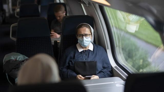 Eine Frau mit Maske im Zug