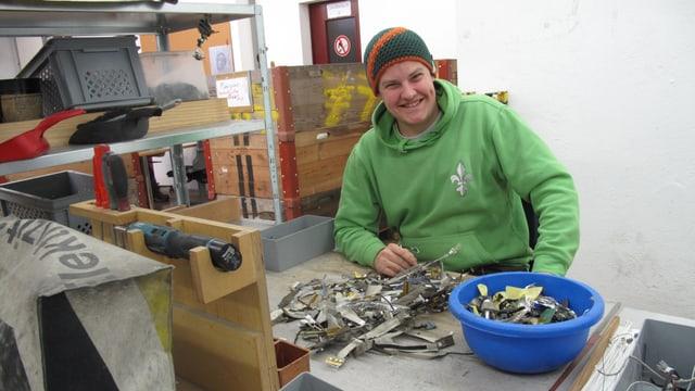 Ein junger sitzt in einer Werkstatt vor einem Haufen Metall.