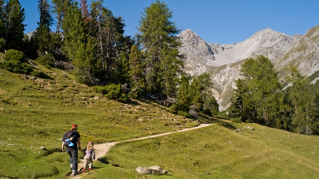 Frau läuft mit Tocher auf einem Wanderweg