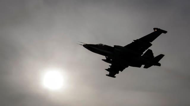 Kampfflugzeug im Gegenlicht der Sonnenscheibe.